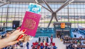 Räcka det hållande UK-passet och UK 5 pund anmärkning Arkivbilder