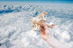 Räcka det lanserande wood flygplanet och blå himmel i molnig dag Arkivbild