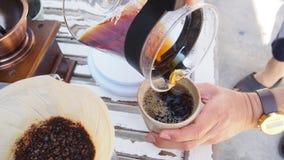 Räcka droppandekaffe, Barista hällande varmvatten över grillat grinded kaffe för brygd för droppande för kaffepulverdanande arkivfoton