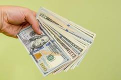 Räcka en räkning för dollar 100 till tittaren Arkivfoto