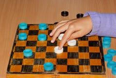 Räcka flickaflyttningar kontrollörerna på schackbrädet Royaltyfri Foto
