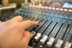 räcka genom att använda den yrkesmässiga ljudsignal blandande konsolen för att kontrollera sounen Fotografering för Bildbyråer