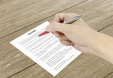 Räcka genom att använda en klassisk pennhandstil på ett meritförteckningpapper Arkivbild