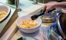 Räcka genom att använda kök den svarta plast- tången till den frasiga räkasprickan för hackan arkivbild
