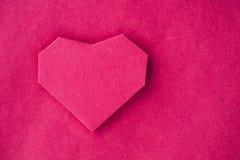 Räcka - gjord pappers- hjärta på kraft som är pappers- som bakgrund. Arkivfoto