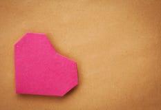 Räcka - gjord pappers- hjärta på kraft som är pappers- som bakgrund. Arkivbild