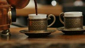 Räcka hällande svart kaffe från turk in i kaffekoppen lager videofilmer