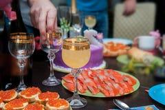 Räcka hällande vitt vin över äppeljuice som tjänas som på tabellen med den läckra maten Vänlycka, medan tycka om äta middag mat C arkivfoto