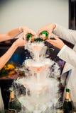 Räcka hälld champagne som är stigande från vinexponeringsglas och, går till set Arkivbilder