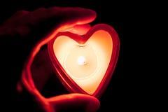 Räcka hållande brinna stearinljushjärta Arkivfoton