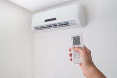 Räcka hållande fjärrkontroll för luftkonditioneringsapparat på den vita väggen royaltyfri foto
