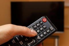 Räcka hållande fjärrkontroll för television som väljer kanalen i TV Arkivbild
