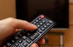 Räcka hållande fjärrkontroll för television som väljer kanalen i TV Arkivfoton