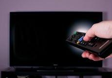 Räcka hållande fjärrkontroll för TV Arkivbild