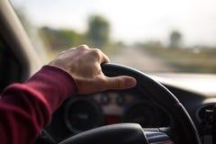 Räcka hållande på det svarta styrninghjulet, medan köra i bilen Arkivbild