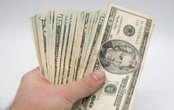 Räcka hållande pengar, amerikan tjugo dollar räkningar på en vitbac Royaltyfri Fotografi