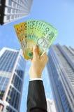 Räcka hållande pengar - australiska dollar - med byggnadsbakgrund Arkivbild