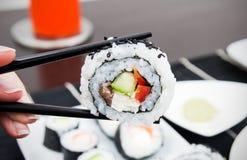 Räcka hållande sushi på pinnar Royaltyfri Bild