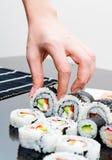 Räcka hållande sushi på svart bakgrund Arkivfoton