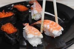 Räcka hållande sushipinnar på en trätabellbakgrund för svart platta Royaltyfri Fotografi