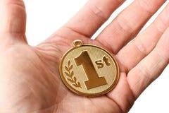 Räcka hållande ut ett 1st ställe det guld- emblemet Royaltyfria Foton