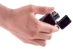 Räcka hållen den hållande tändaren, på vit bakgrund Arkivfoto