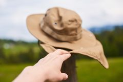 Räcka hållen den turist- hatten som fladdrar i vinden Arkivfoto