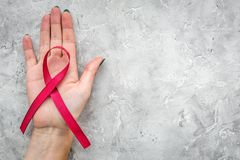 Räcka hållen det röda bandet för HIV, HJÄLPMEDEL, drogmissbruk och anoreximedvetenhet på copyspace för bästa sikt för grå färgste Arkivbilder