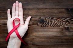 Räcka hållen det röda bandet för HIV, HJÄLPMEDEL, drogmissbruk och anoreximedvetenhet på mörk träcopyspace för bästa sikt för bak Royaltyfri Fotografi