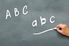 Räcka handstil på en svart tavla bokstavsabcen Arkivfoto