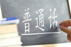 Räcka handstil på en svart tavla i en kinesisk grupp Arkivfoto