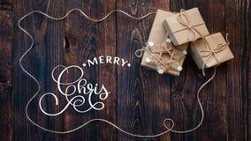 Räcka handstil vit för animeringkalligrafi för glad jul text för bokstäver på mörk träbakgrund med gåvor och vektor illustrationer
