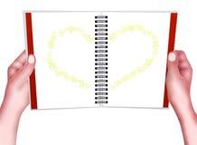 Räcka innehav som en röra sig i spiralanteckningsbok med hjärta mönstrar Arkivfoto