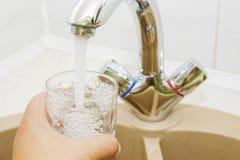 Räcka innehav som ett exponeringsglas av bevattnar hällt från kökvattenkranen Arkivbilder