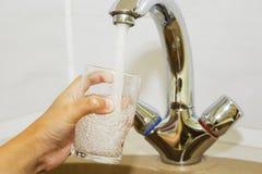 Räcka innehav som ett exponeringsglas av bevattnar hällt från kökvattenkranen Fotografering för Bildbyråer