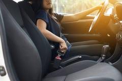 Räcka kvinnachaufförfästande eller sättasäkerhetsbältet i bil-, trans.- och medelsäkerhetsbegrepp royaltyfria bilder