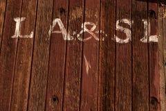 Räcka målade vita bokstäver på sida av övergiven yttersida för caboosen för drevjärnvägbilen arkivbilder