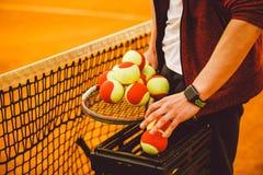Räcka mannen som rymmer en tennisracket och många mål Korg för tennisbollar, fotografering för bildbyråer