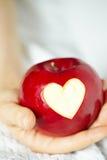Räcka med äpplet, som klippte hjärta royaltyfri foto