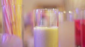 Räcka mellanlägg ett sugrör in i ett exponeringsglas med en coctail och tar det stock video