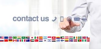 Räcka pekskärmskärm med globalt kontaktar oss begreppstext, f Royaltyfri Foto