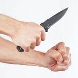 Räcka positionen till attack med en armékniv på vit bakgrund Arkivbilder