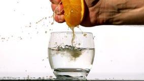 Räcka sammanpressning av fruktsaft av apelsinen in i exponeringsglas av vatten Arkivbilder