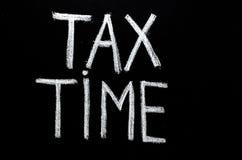 Räcka skriftlig ` för tid för uttrycks`-skatt på den svart tavlan royaltyfri foto