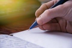 Räcka som skriver en penna i en förskriftsbok, process av en handstil Arkivfoto