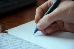 Räcka som skriver en penna i en förskriftsbok, process av en handstil Royaltyfri Fotografi