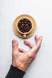Räcka sträckning till en kopp kaffe på en vit bakgrund som hälls Arkivfoton