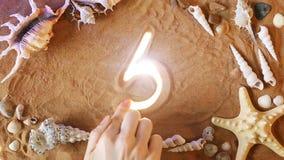 Räcka symbol 5 för teckningsnummer fem i sanden pink scallop seashell Top beskådar lager videofilmer