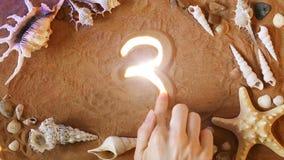 Räcka symbol 3 för teckningsnummer tre i sanden pink scallop seashell Top beskådar stock video
