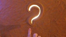 Räcka symbolet för teckningsfrågefläcken i sanden pink scallop seashell Top beskådar arkivfilmer